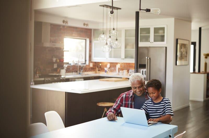 Avô e neto que sentam-se em torno da tabela em casa que usa o portátil junto fotos de stock