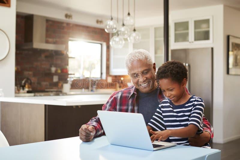 Avô e neto que sentam-se em torno da tabela em casa que usa o portátil junto foto de stock royalty free