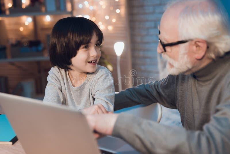 Avô e neto que sentam-se no portátil na noite em casa imagens de stock royalty free