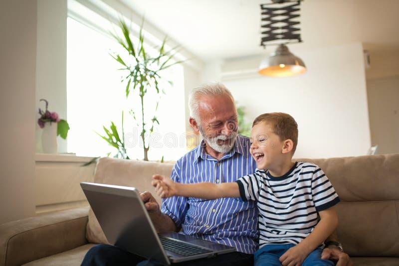 Avô e neto que usa o portátil fotos de stock