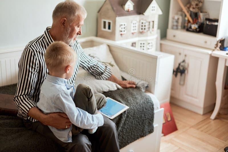 Avô e neto que usa a tabuleta digital ao sentar-se no sofá imagem de stock royalty free