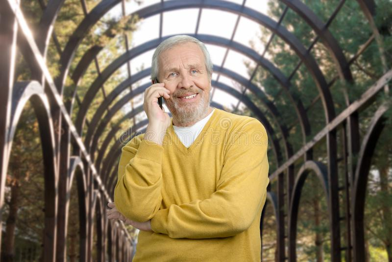 Avô idoso de sorriso que fala no telefone na estufa imagem de stock royalty free