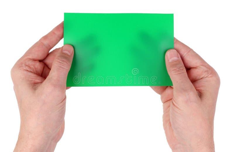 Avô idoso do homem que guarda o cartão de papel verde vazio da página dentro foto de stock