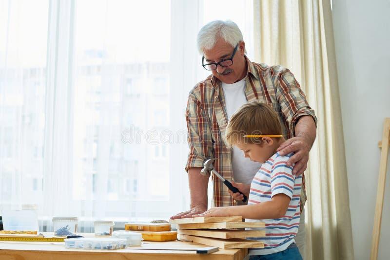 Avô loving e Little Boy que fazem modelos de madeira junto foto de stock royalty free