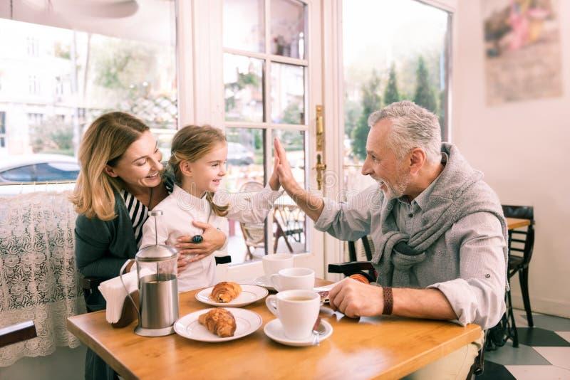 Avô moderno que dá a altamente cinco sua neta pequena bonito fotografia de stock royalty free