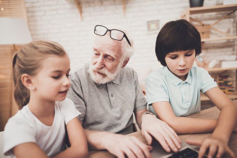 Avô, neto e neta em casa O vovô e as crianças estão usando o portátil fotos de stock royalty free