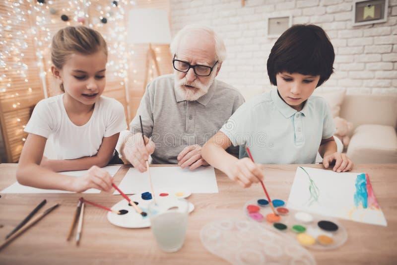 Avô, neto e neta em casa O vovô está ajudando a pintura das crianças foto de stock