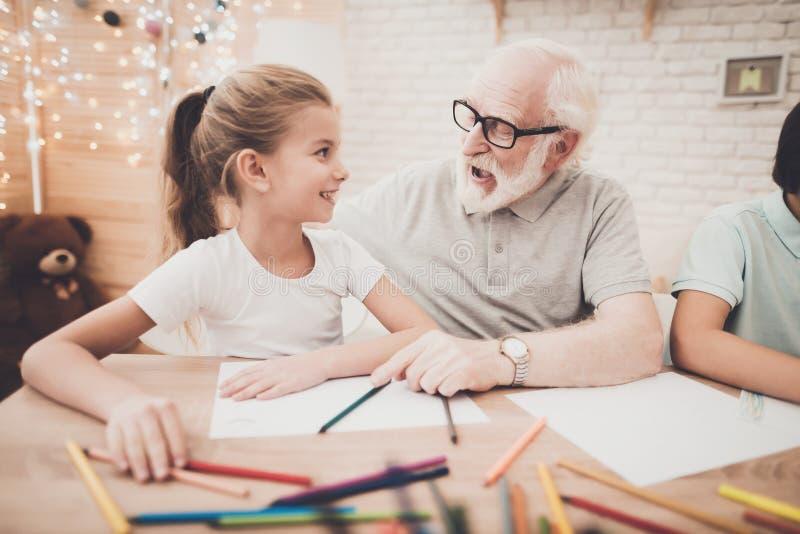 Avô, neto e neta em casa O vovô está ajudando a tração das crianças imagens de stock royalty free