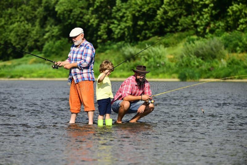 Avô, pai e neto pescando junto Pescadores da família que pescam com carretel de gerencio imagem de stock royalty free