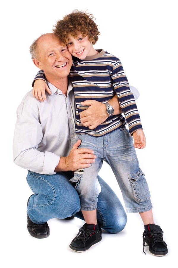 Avô que abraça seu neto imagem de stock