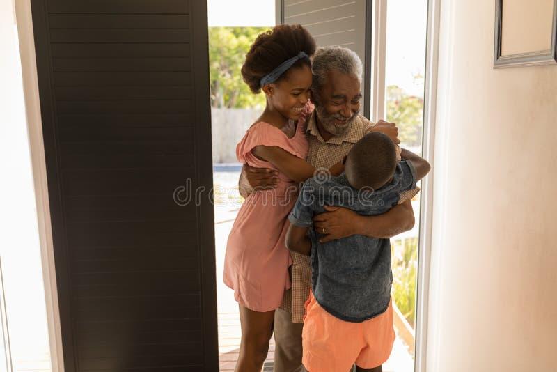 Avô que abraça seus netos em casa fotografia de stock