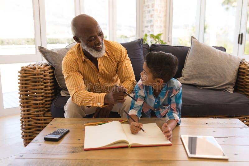 Avô que ajuda seu neto com trabalhos de casa na sala de visitas fotografia de stock royalty free