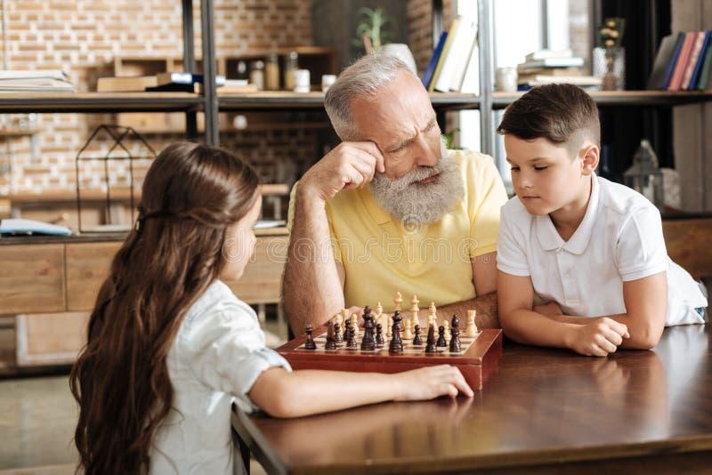 Avô que dá a seu neto uma ponta no jogo de xadrez fotografia de stock royalty free