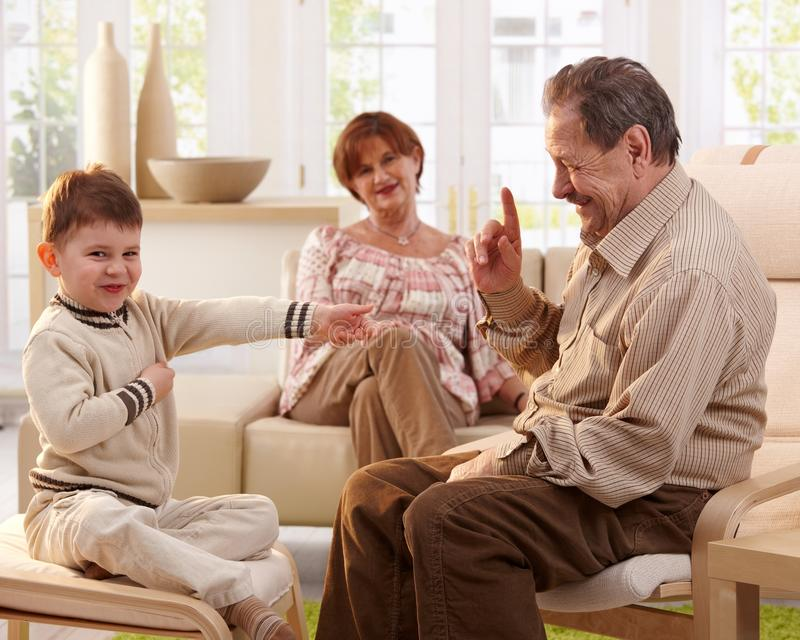 Avô que diz dizendo uma história ao neto imagem de stock royalty free