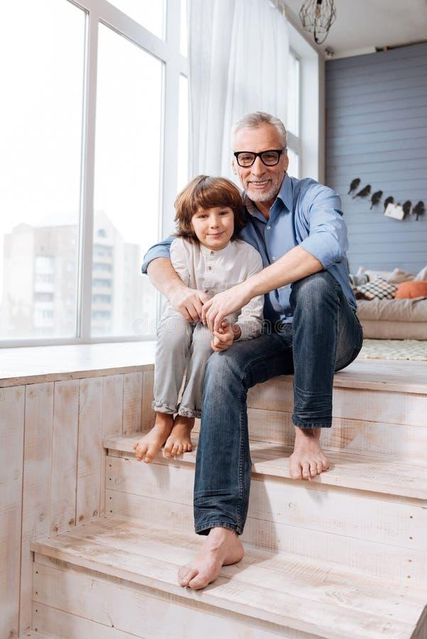 Avô agradável e neto deleitados que sentam-se nas escadas fotografia de stock