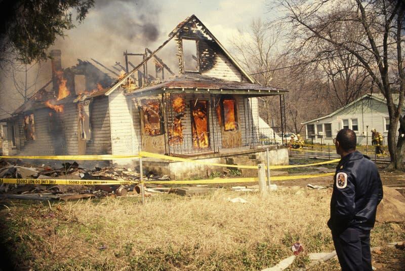 Av - arbetsuppgiftbrandmannen håller ögonen på en vakant husbrand royaltyfri bild