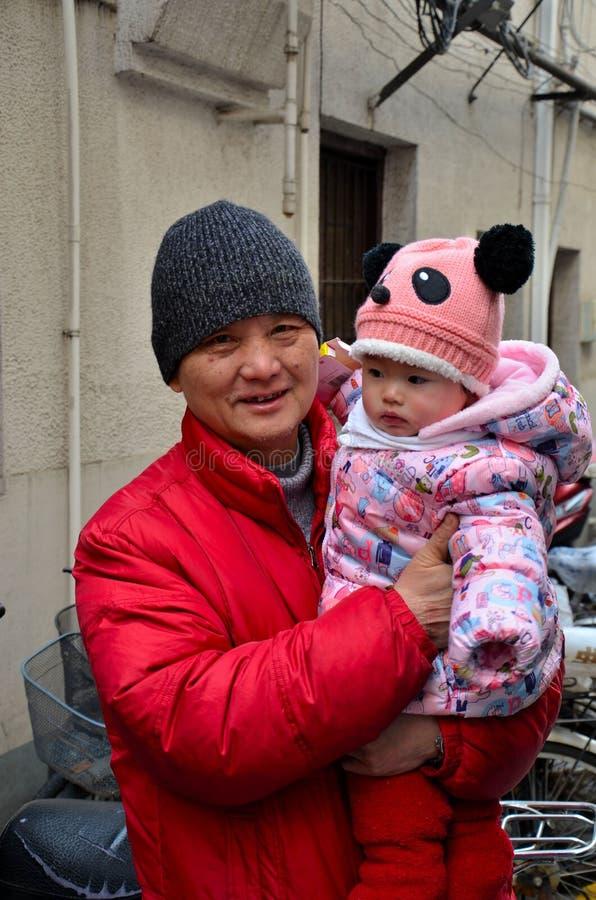 Avô chinês orgulhoso com o bebê empacotado do inverno imagem de stock royalty free