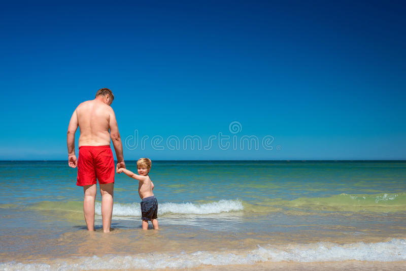 Avô com o neto na praia fotografia de stock