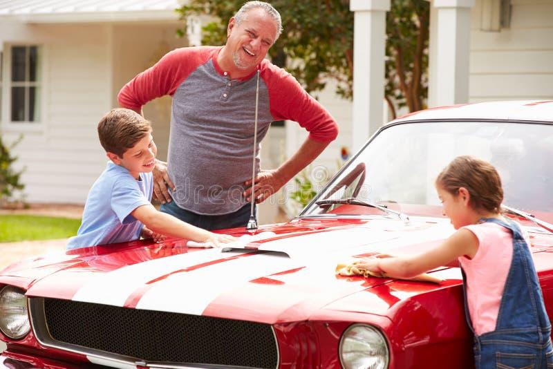 Avô com os netos que limpam o carro clássico restaurado foto de stock royalty free