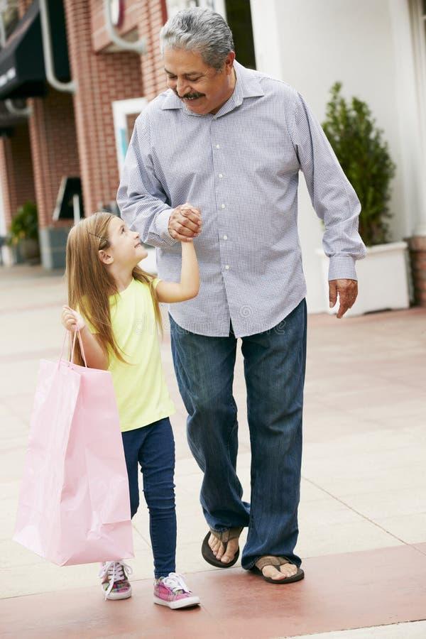 Avô com os sacos de compras levando da neta imagens de stock royalty free