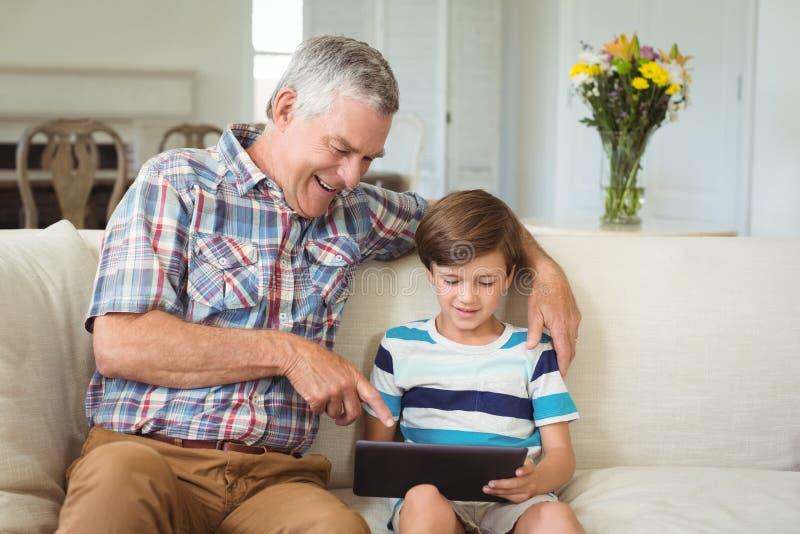 Avô com seu neto que usa a tabuleta digital no sofá fotografia de stock