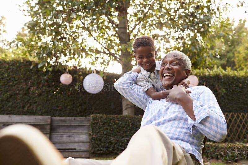 Avô de abraço do menino preto novo que senta-se no jardim imagem de stock