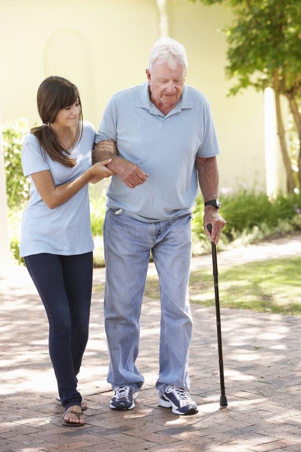 Avô de ajuda da neta adolescente para fora na caminhada fotos de stock royalty free