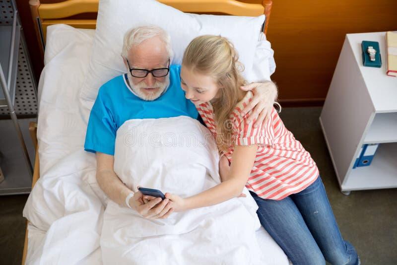Avô e criança que usa o smartphone foto de stock royalty free