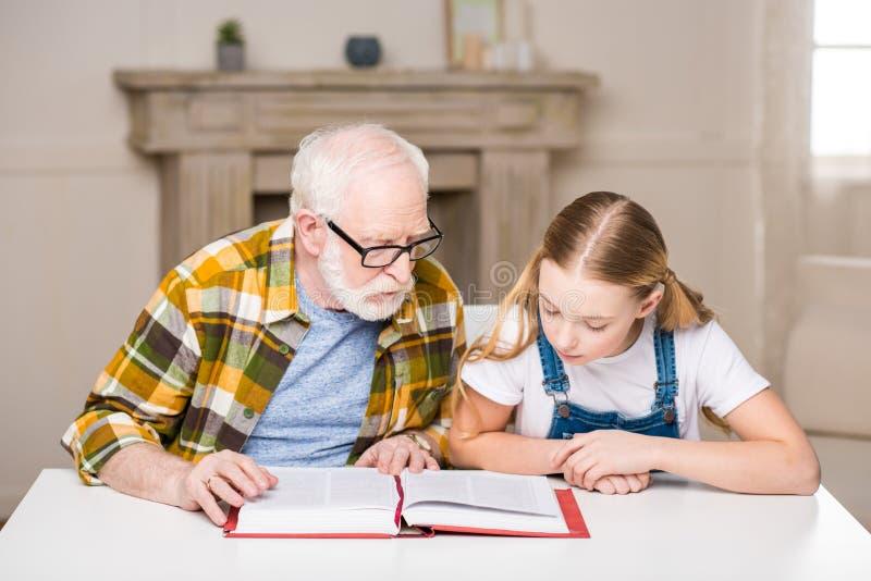 Avô e neta que sentam-se na tabela foto de stock