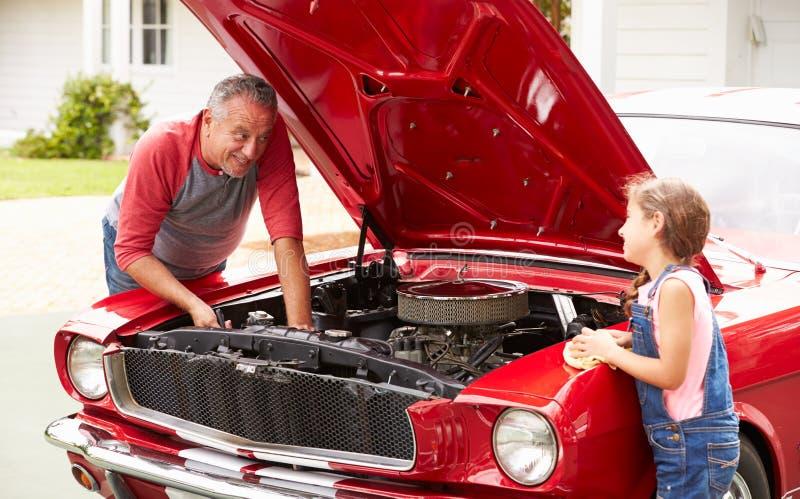 Avô e neta que trabalham no carro clássico imagem de stock