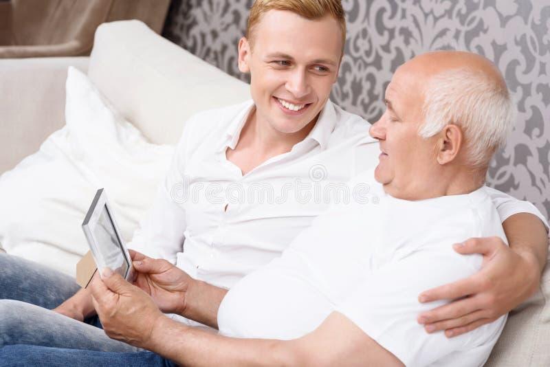 Avô e neto com a foto no quadro imagem de stock