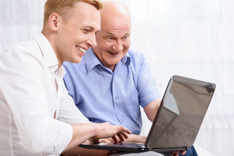Avô e neto com portátil imagem de stock royalty free