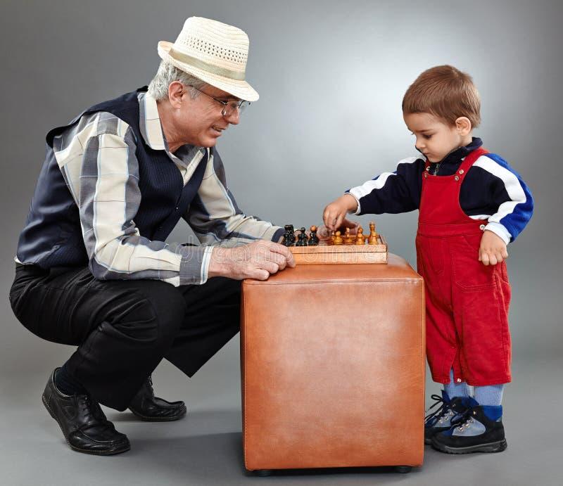 Avô e neto que jogam a xadrez foto de stock
