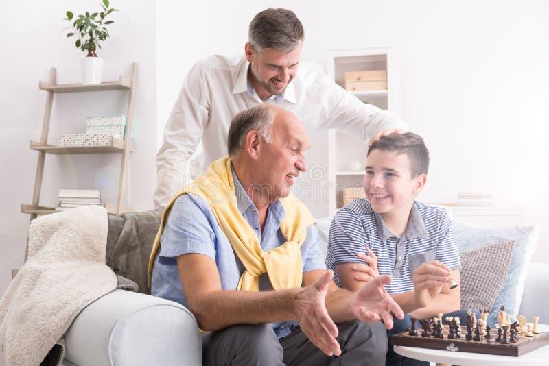 Avô e neto que jogam a xadrez imagem de stock