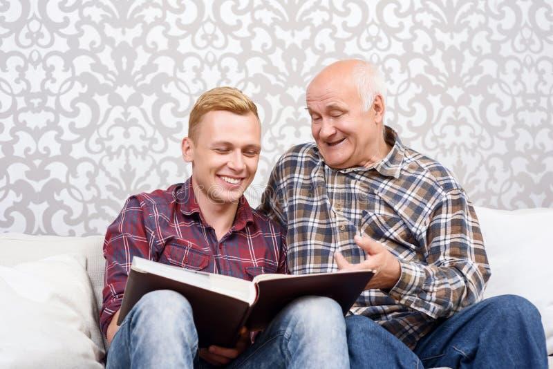 Avô e neto que sentam-se com álbum fotos de stock