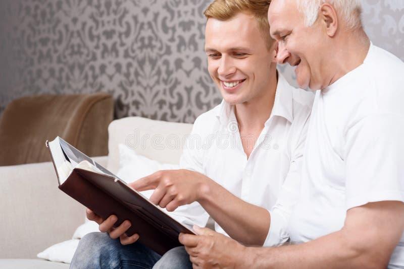 Avô e neto que sentam-se com álbum imagens de stock royalty free
