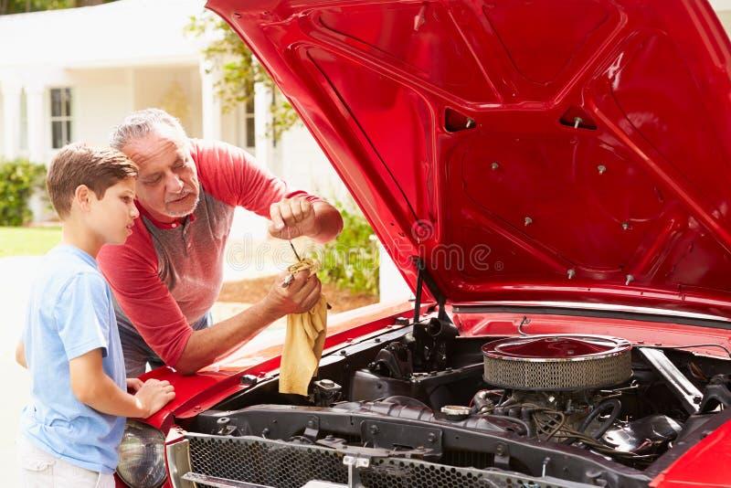 Avô e neto que trabalham no carro clássico restaurado imagens de stock royalty free