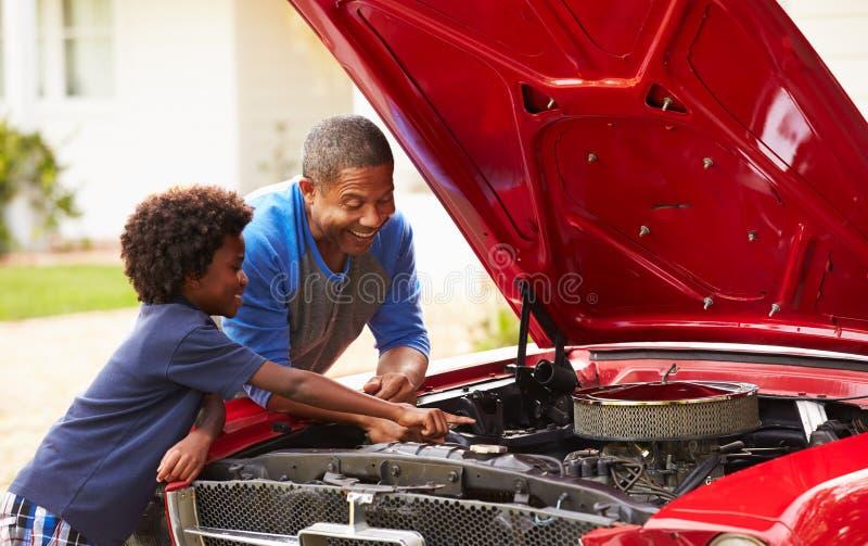 Avô e neto que trabalham no carro clássico restaurado fotografia de stock royalty free
