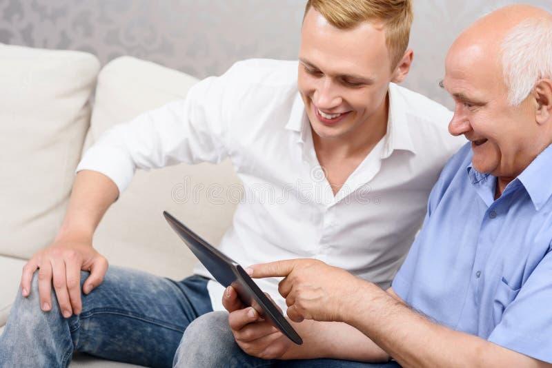 Avô e neto que usa a tabuleta junto imagens de stock