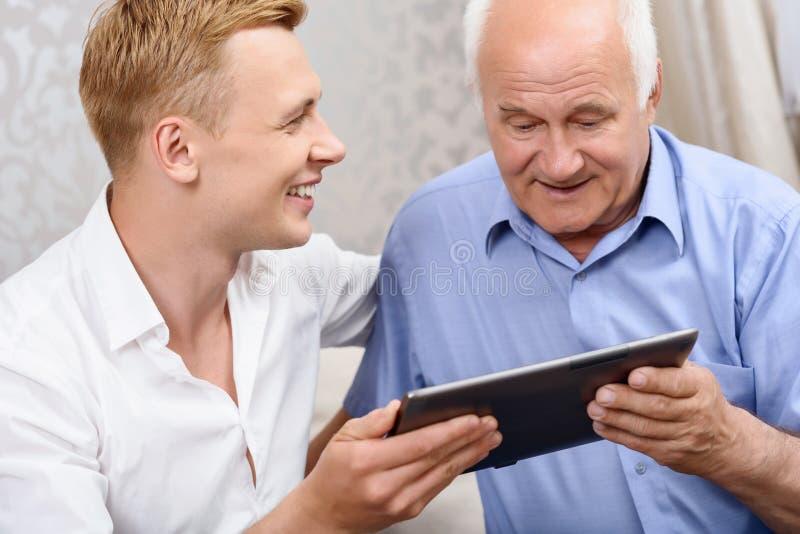 Avô e neto que usa a tabuleta junto fotografia de stock