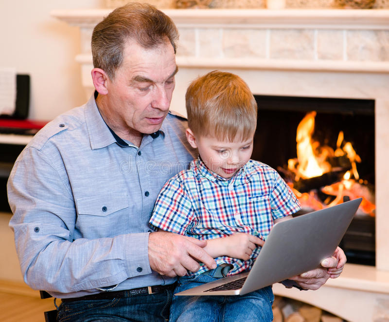 Avô e neto que usa um portátil foto de stock