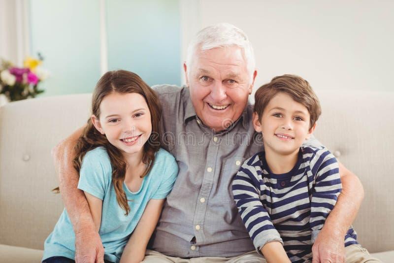 Avô e netos que sentam-se junto no sofá foto de stock