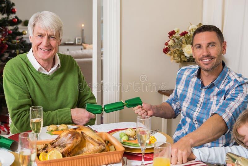 Avô e pai de sorriso que puxam biscoitos do Natal fotografia de stock