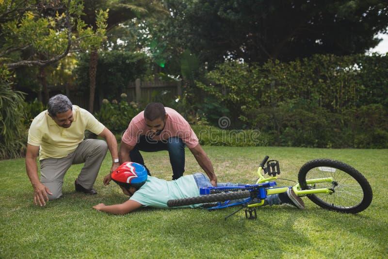 Avô e pai que ajudam o menino caído com bicicleta imagem de stock royalty free