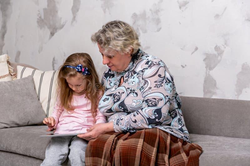 A av? e sua neta pequena est?o olhando filmes junto e est?o jogando-os no dispositivo ao sentar-se no sof? imagens de stock royalty free