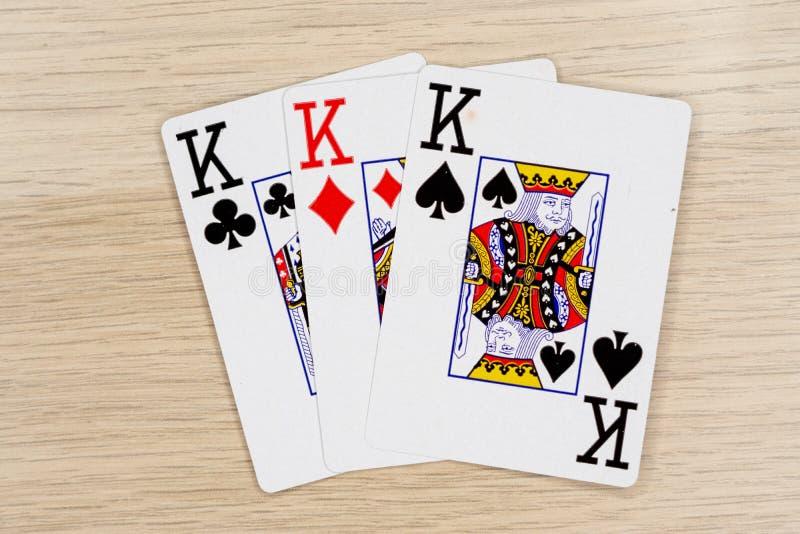 3 av en sort gör till kung - kasinot som spelar pokerkort arkivbilder