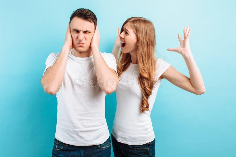 Av ett ungt par aggressiv kvinna som ropar på en man, en man som täcker hans öron med hans händer, på en blå bakgrund arkivbilder