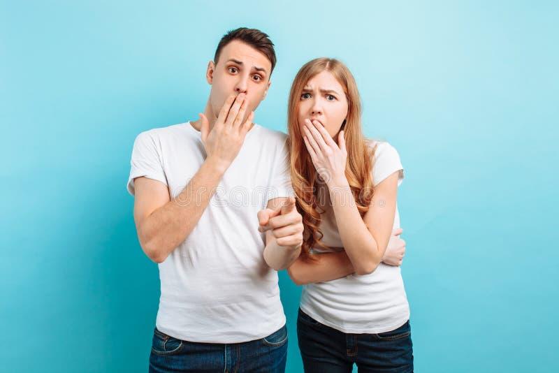 Av ett ungt par skrämd man och kvinna som rymmer händer nära munnen, skrämda uttryck, på en blå bakgrund royaltyfri foto