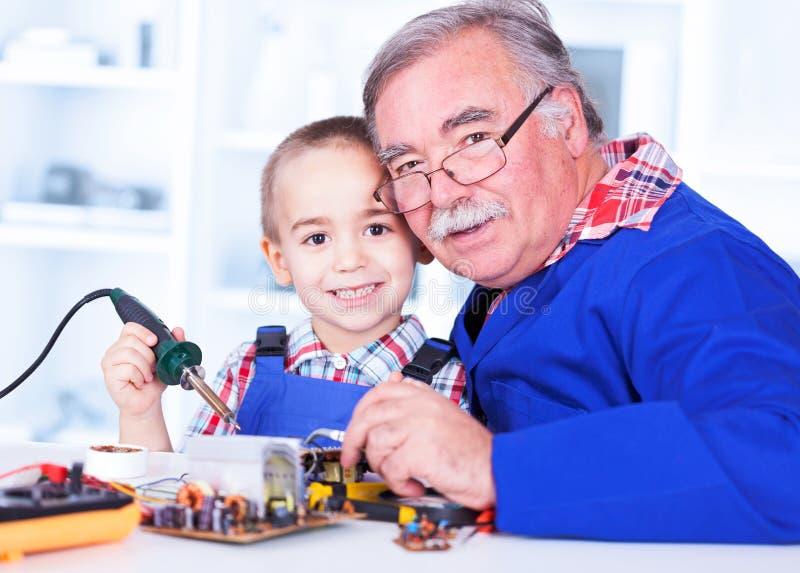 Avô feliz e neto que trabalham junto na oficina foto de stock