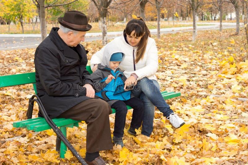 Avô, mãe e rapaz pequeno em um banco de parque imagem de stock